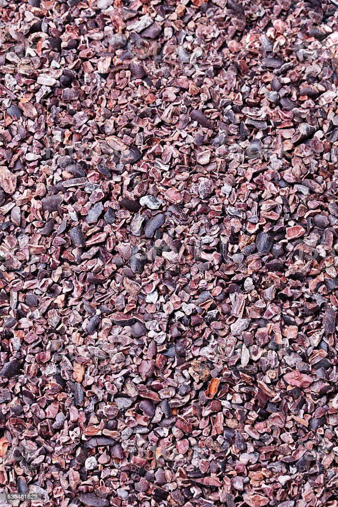 Raw crushed cocoa beans, nibs background Copy space Top view stock photo