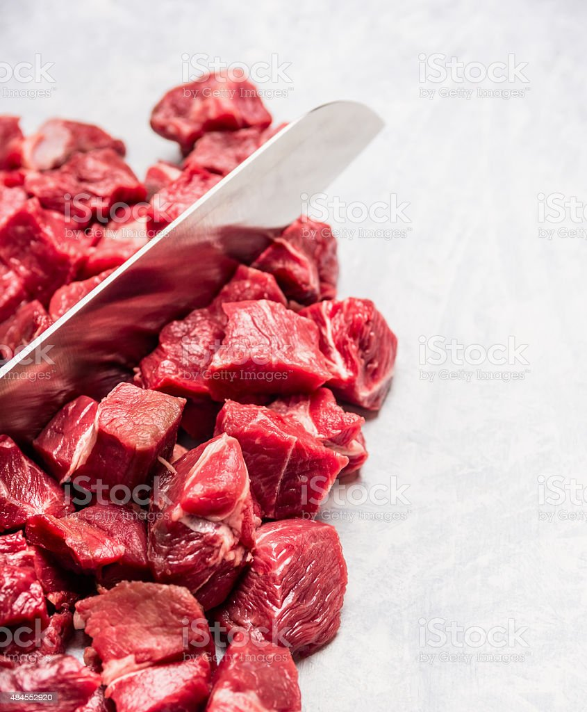 raw  cubes chopped meat for goulash or stew with knife stock photo