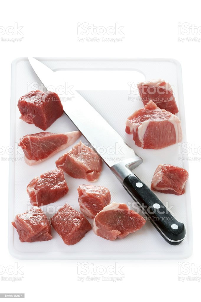 raw cubes lamb on a chopping board with knife isolated royalty-free stock photo