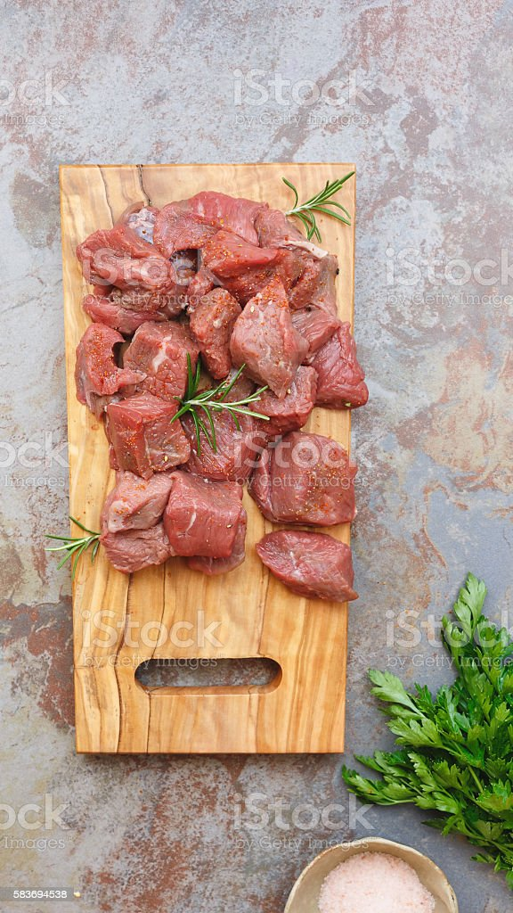 Raw diced meat with herbs and spices, cooking preparation stock photo