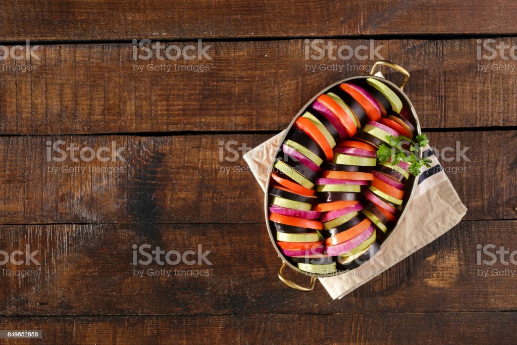 Raw dish ratatouille in pan on wooden table with border stock photo