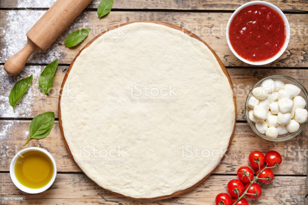 Raw dough for pizza with ingredient: tomato sauce, dough, mozzarella, tomatoes, basil, olive oil, spices served on rustic wooden table. Aerial shot, copyspace for text. stock photo