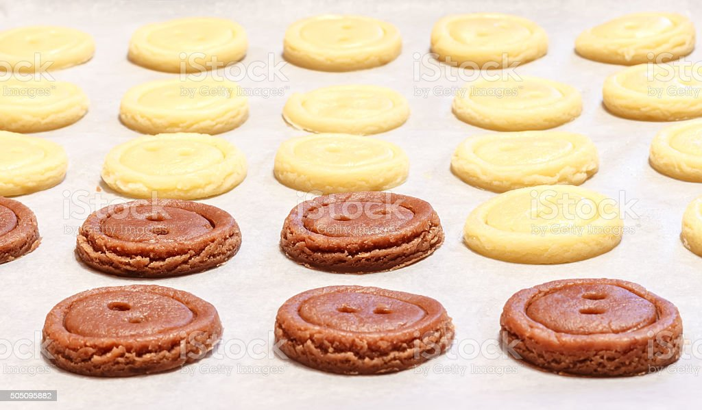 Raw dough. Yellow and brown cookies buttons. stock photo