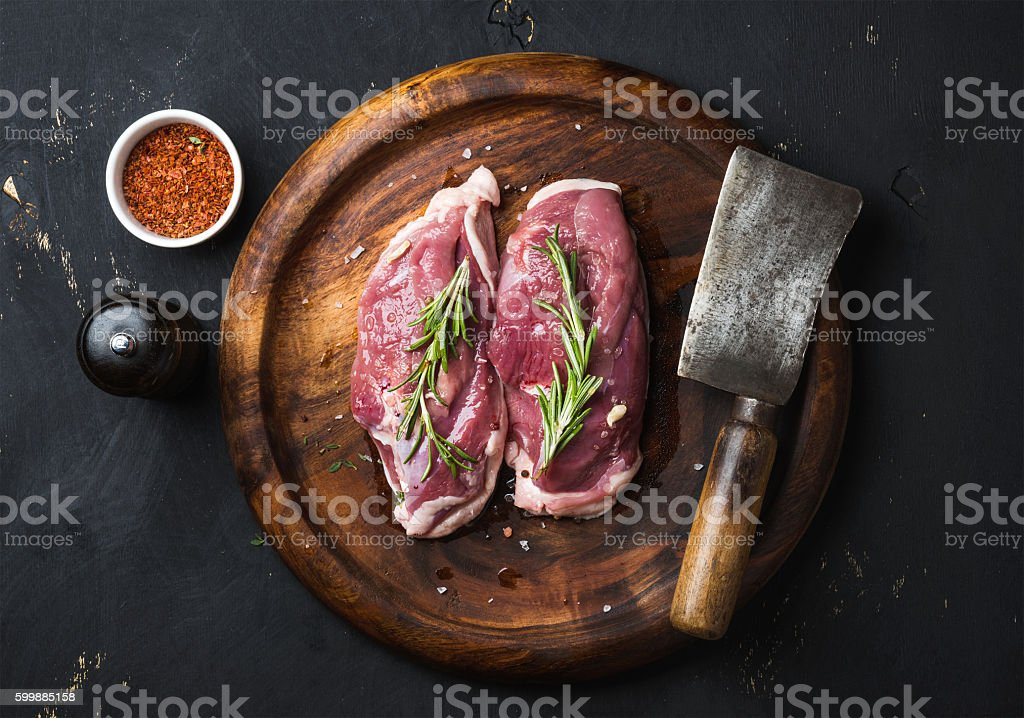 Raw duck breast with rosemary, spices on dark wooden tray stock photo