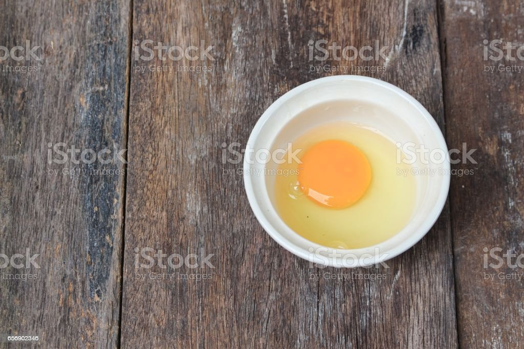 Raw egg in a bowl  on wooden table stock photo