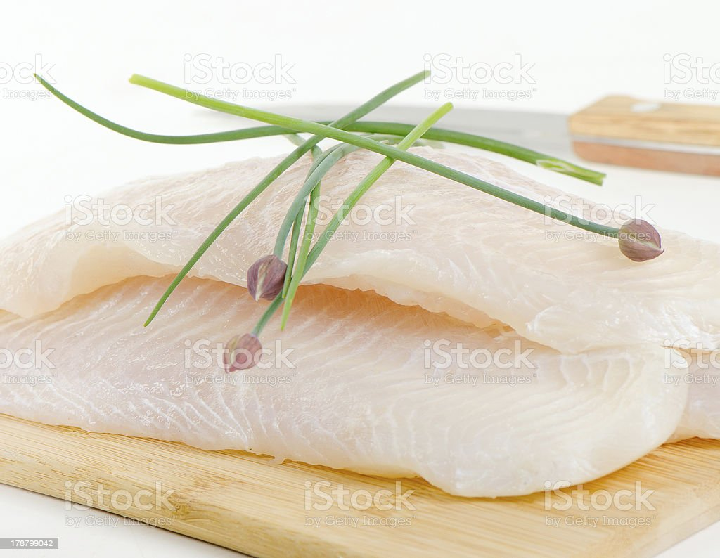 A raw fillet of white fish with fresh chives stock photo