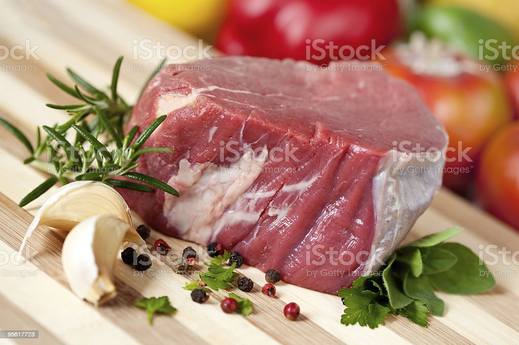 Raw fillet steak with garlic, herbs and spices on a board stock photo