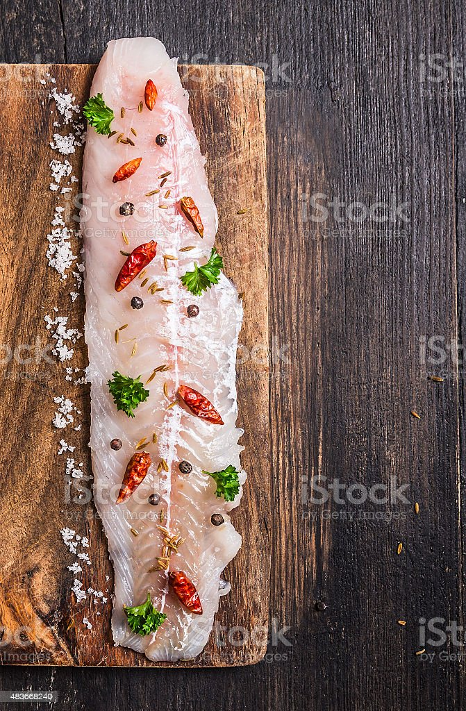 raw Fish fillet with herbs and spices on cutting board stock photo