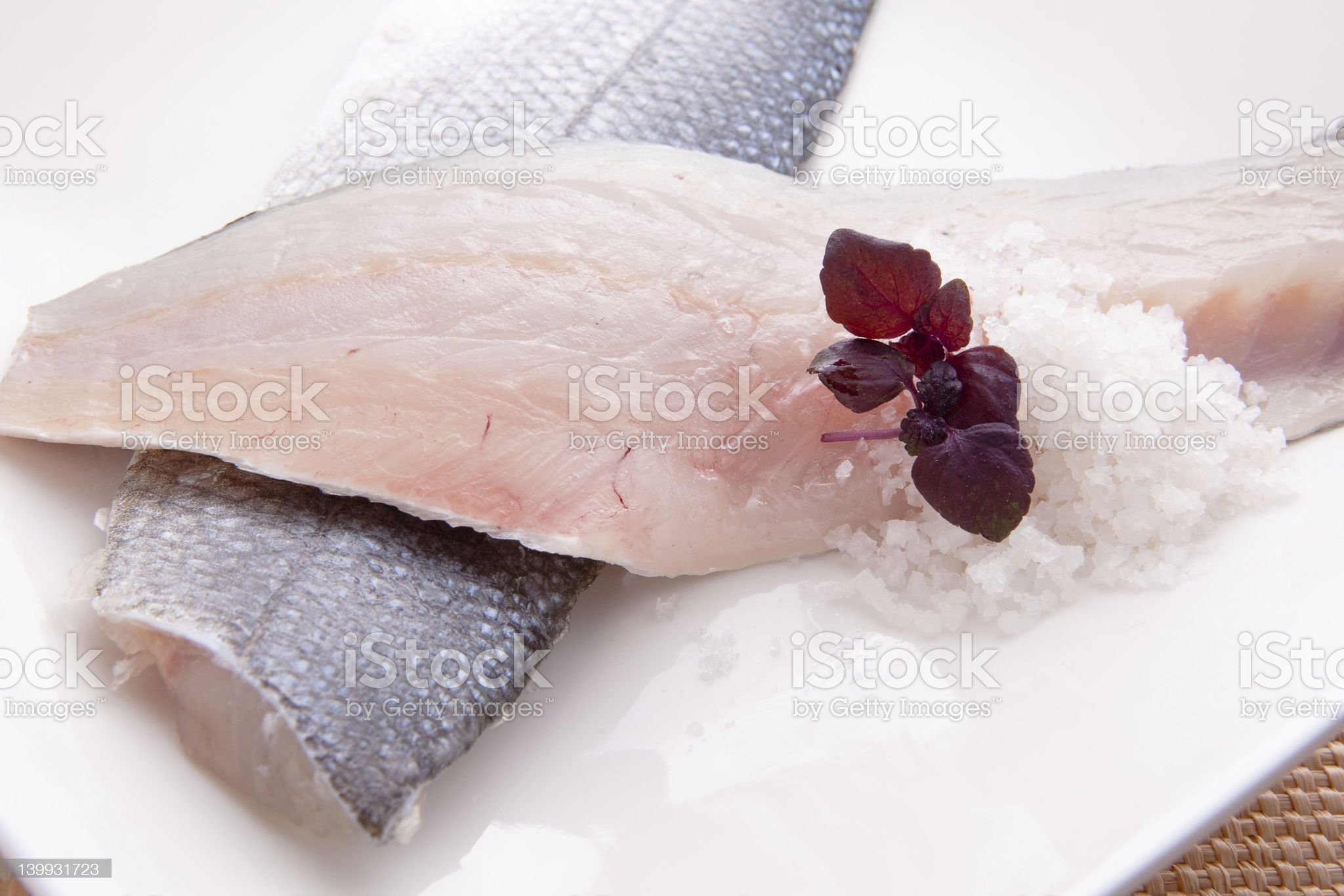 Raw fish fillets on white plate with rice and garnish royalty-free stock photo