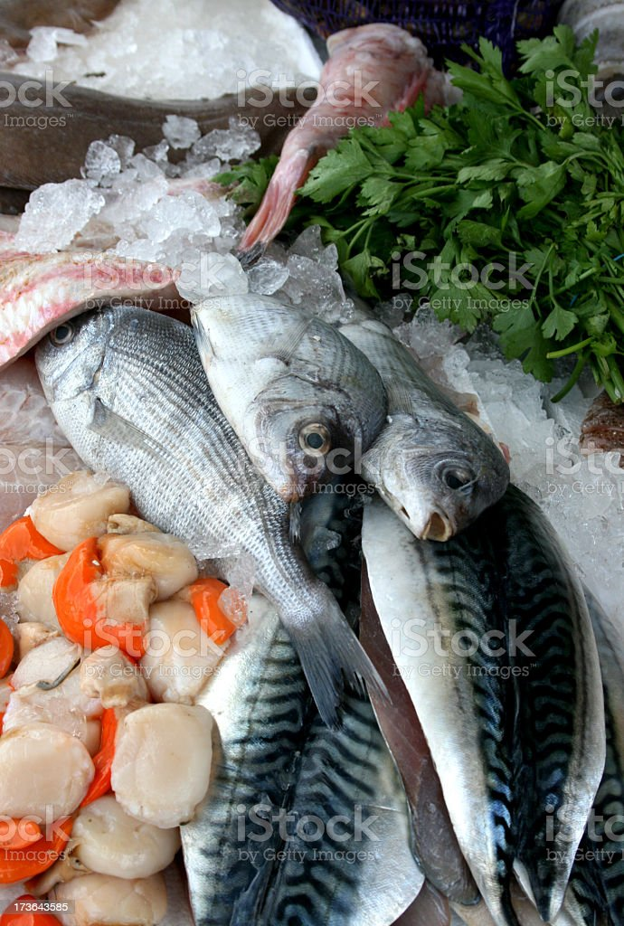 Raw fish on ice, greens, and vegetables royalty-free stock photo