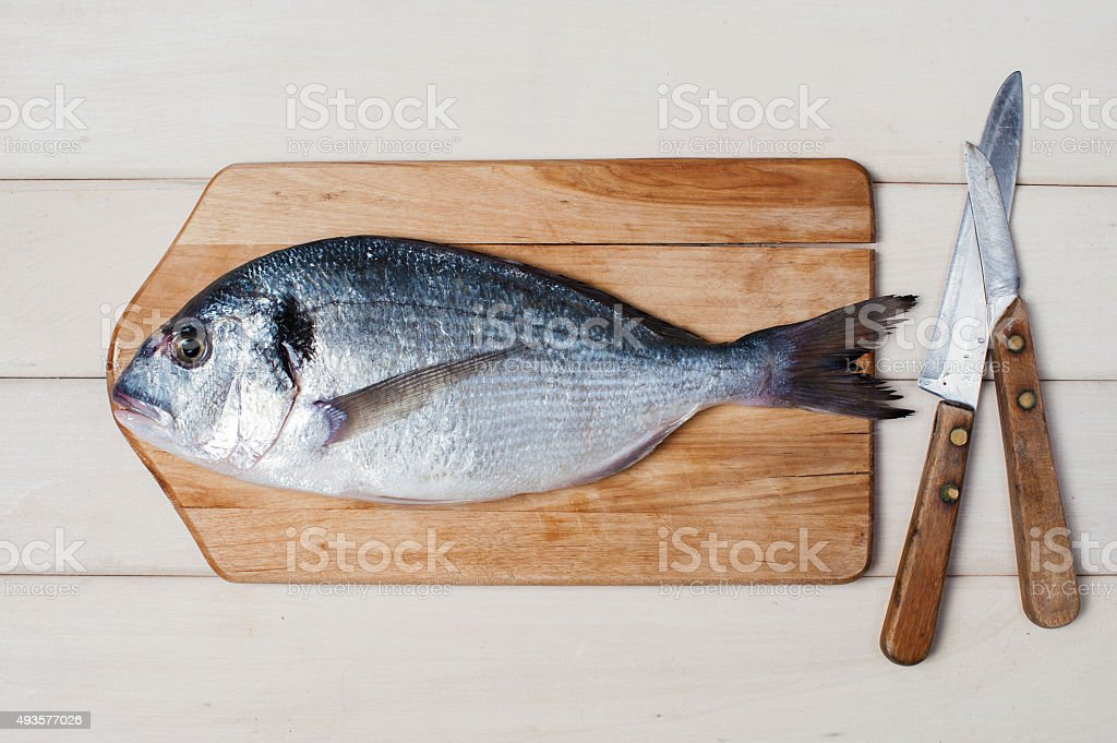 Raw fish on the white wooden table stock photo