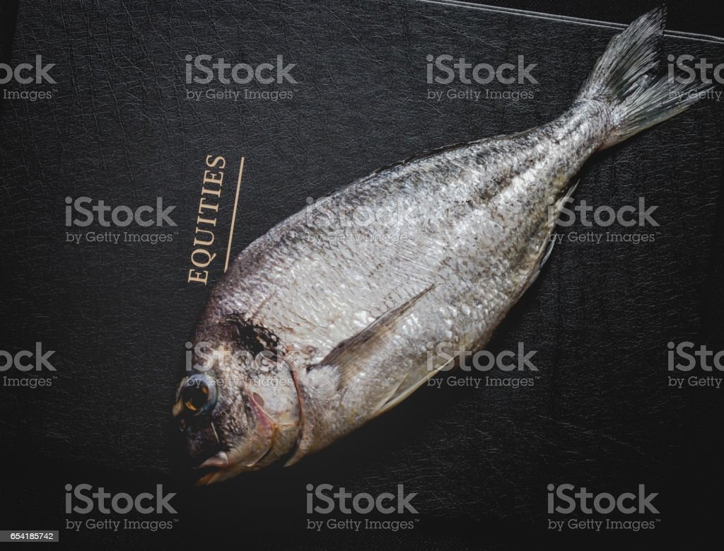 Raw fresh bream on shares equities prices letters black background stock photo