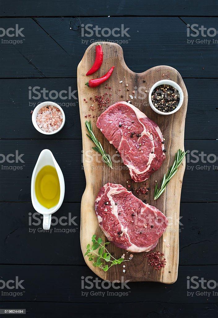 Raw fresh meat Ribeye steak entrecote and seasonings on cutting stock photo