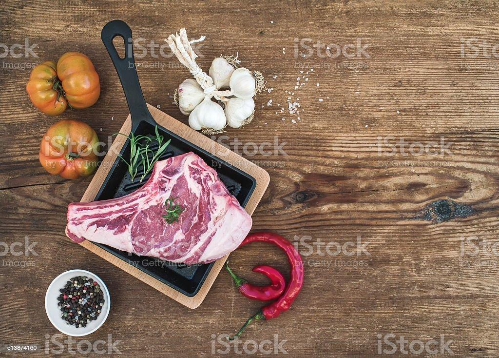 Raw fresh meat ribeye steak with pepper, salt, chili, garlic stock photo