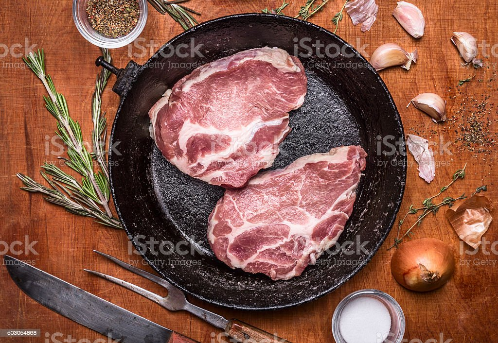 raw fresh pork steaks old cast-iron frying pan close up stock photo