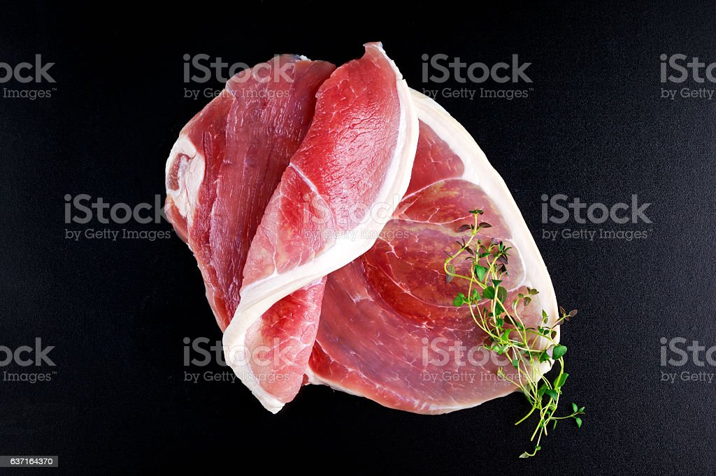 Raw gammon steak on black background with thyme stock photo