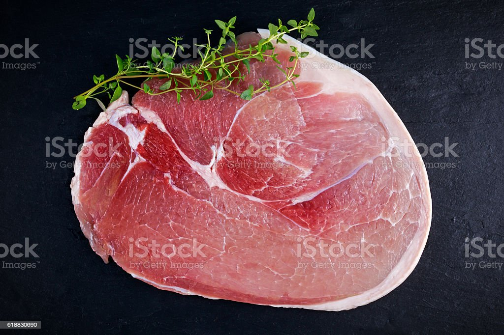 Raw gammon steak on black stone background stock photo