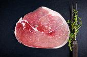 Raw gammon steak on black stone background