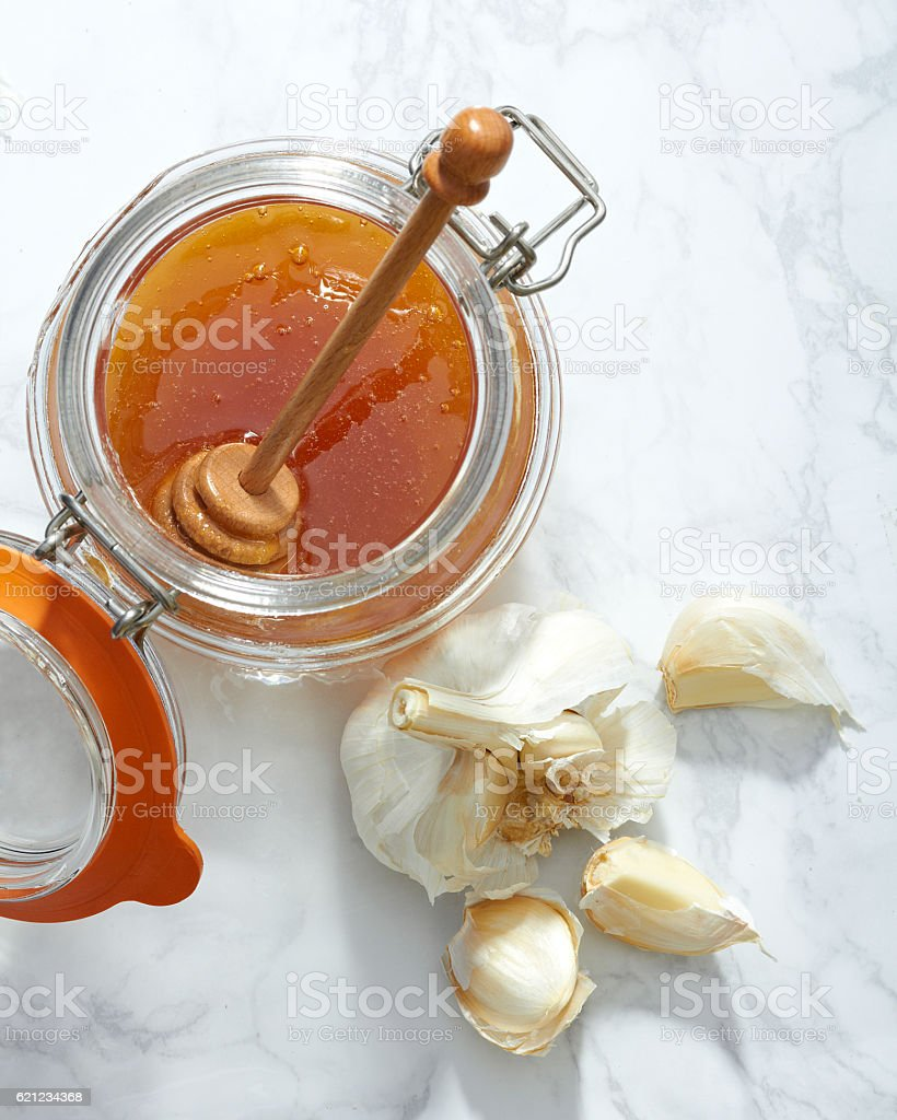 Raw Garlic and a Honey Jar Viewed from Above stock photo