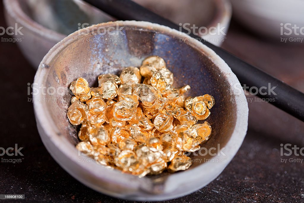 Raw gold in bowl straight from the mine stock photo