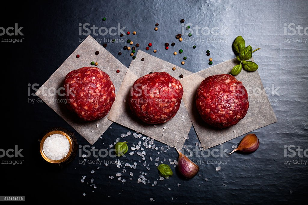 Raw ground beef meat steak cutlets with herbs and spices stock photo