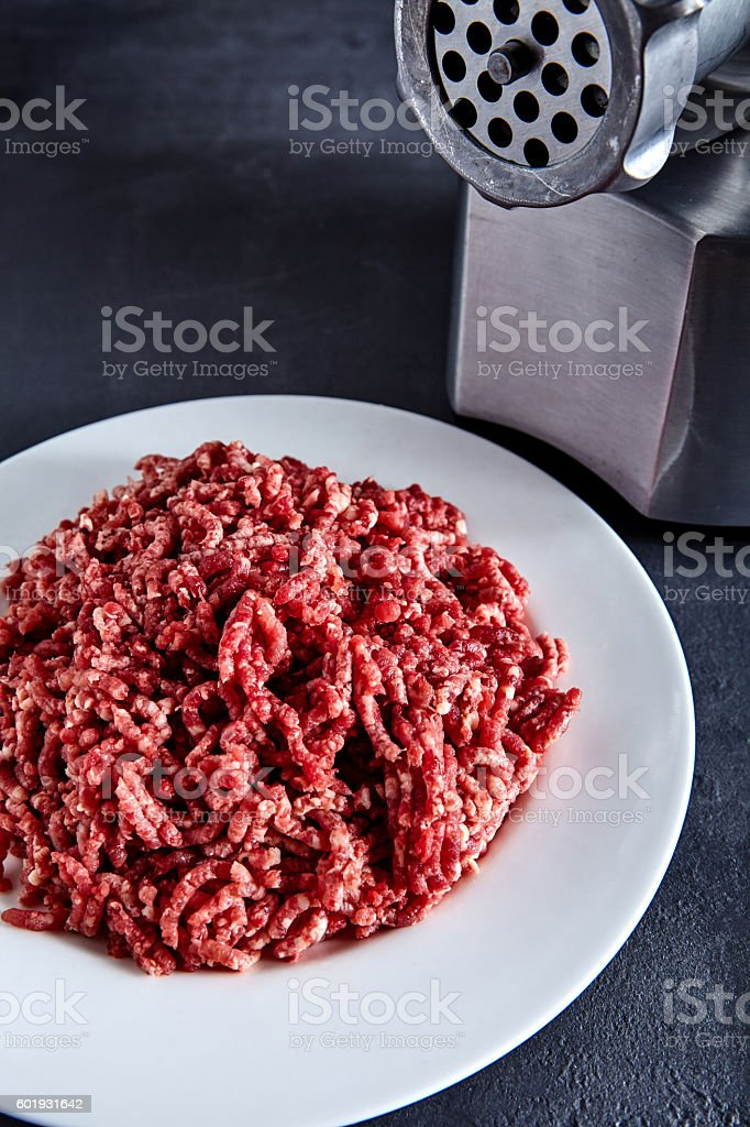 Raw ground beef on a white plate with meat grinder stock photo