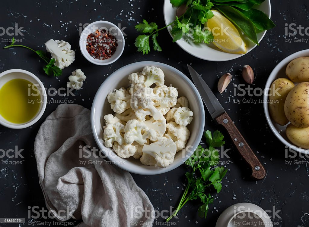 Raw ingredients - cauliflower, potatoes, olive oil and spices stock photo