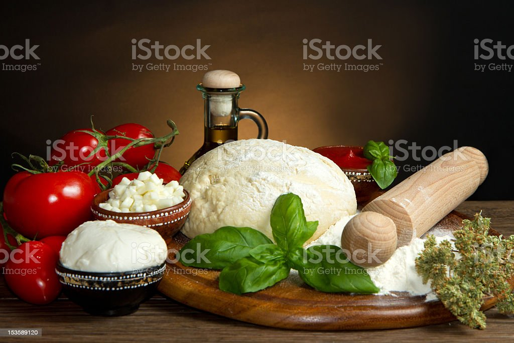 Raw ingredients to make a pizza placed on bench royalty-free stock photo