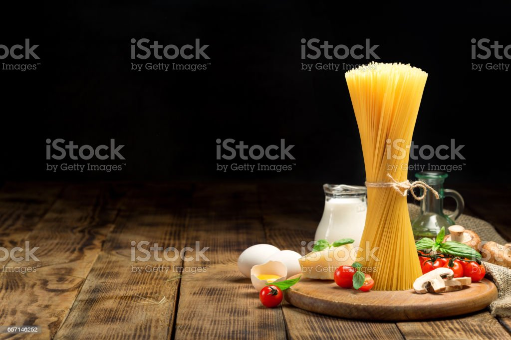 Raw Italian spaghetti with ingredients for cooking Italian pasta on wooden table stock photo