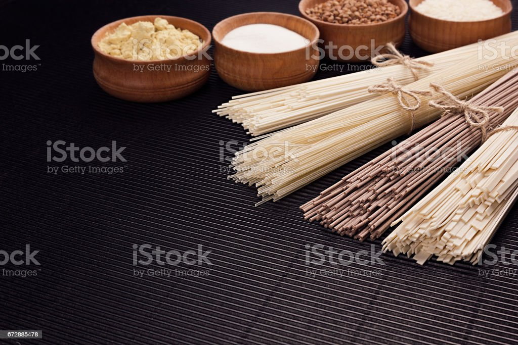 Raw japanese noodles with ingredient in wooden bowls on black striped mat background with copy space. stock photo