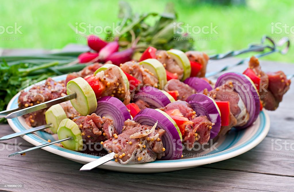 Raw kebabs and vegetables stock photo