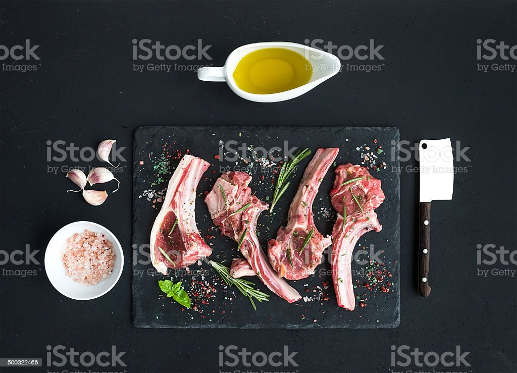 Raw lamb chops. Rack of Lamb with garlic, rosemary and stock photo
