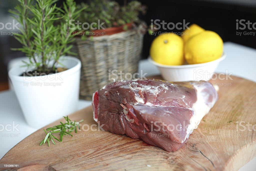 Raw lamb leg meat on the wooden cutting board stock photo