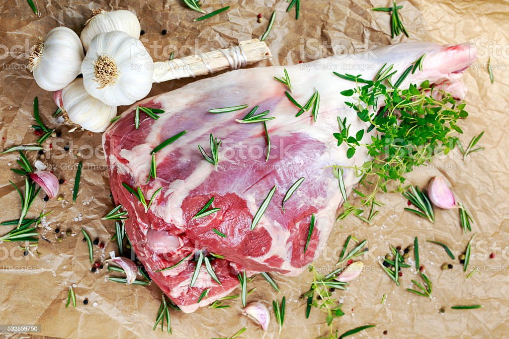 Raw lamb leg on crumpled paper background with herbs stock photo