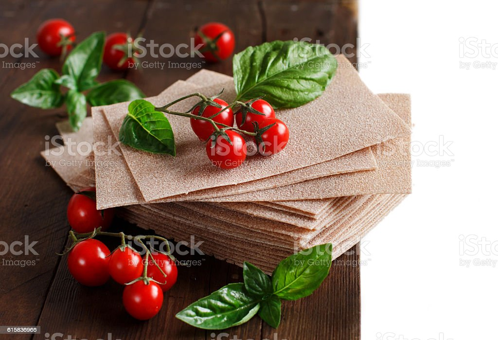 Raw lasagna sheets and cherry tomatoes stock photo