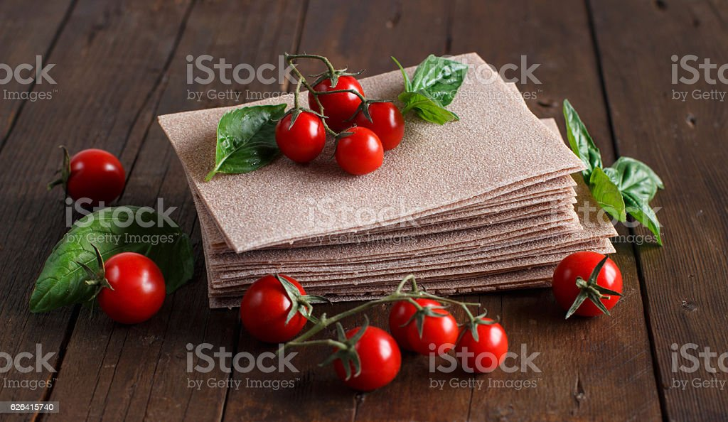 Raw lasagna sheets, basil and cherry tomatoes stock photo