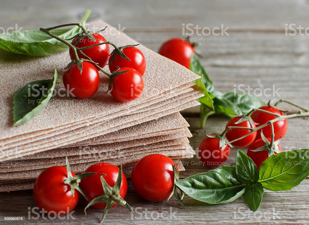Raw lasagna sheets,basil and cherry tomatoes stock photo