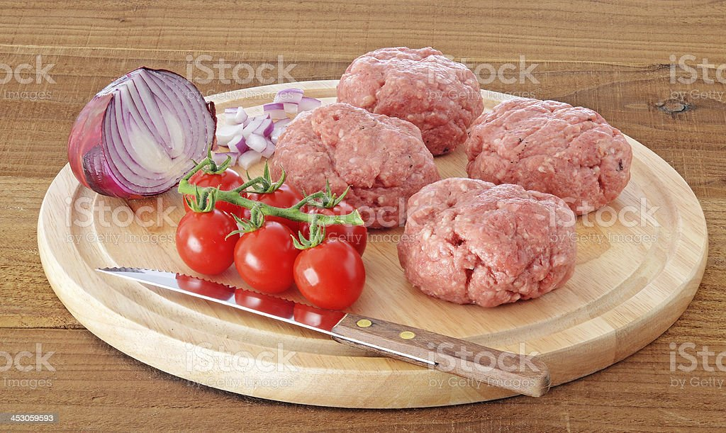 Raw meat burgers on wooden board royalty-free stock photo