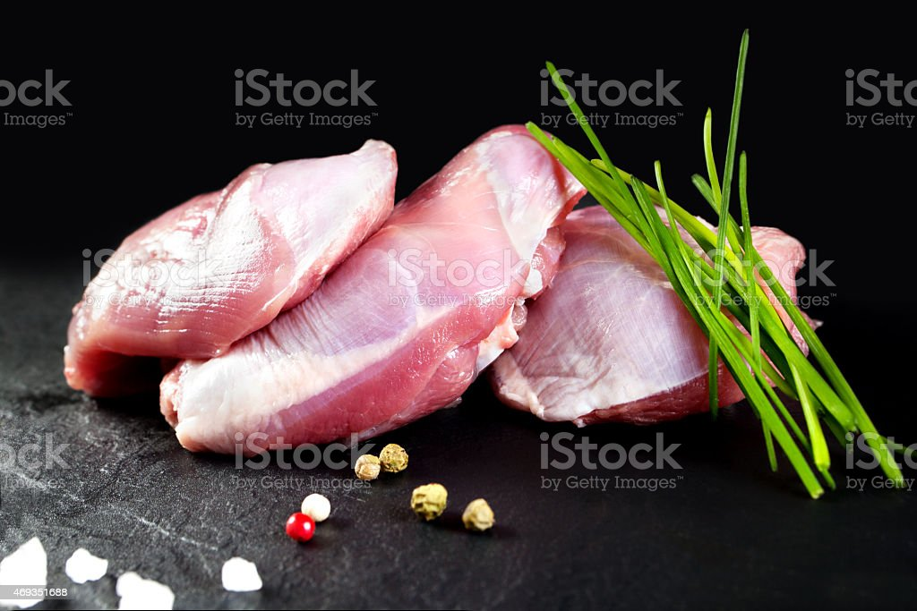 Raw meat. Fresh skinless chicken thighs on black chalkboard background stock photo