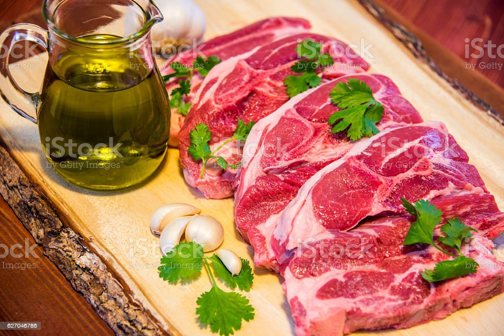 Raw meat on a cutting board with rosemary and spices. stock photo