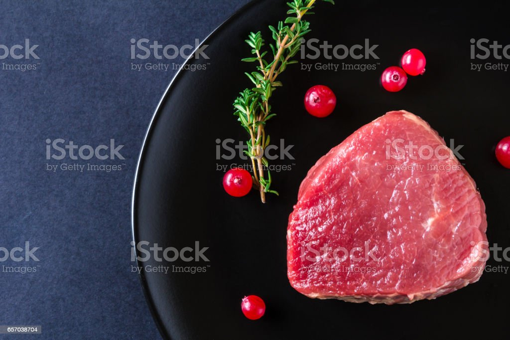 Raw meat on black plate and dark background stock photo
