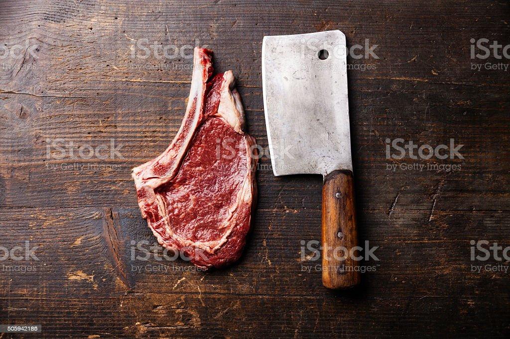 Raw meat Ribeye Steak on bone and cleaver stock photo
