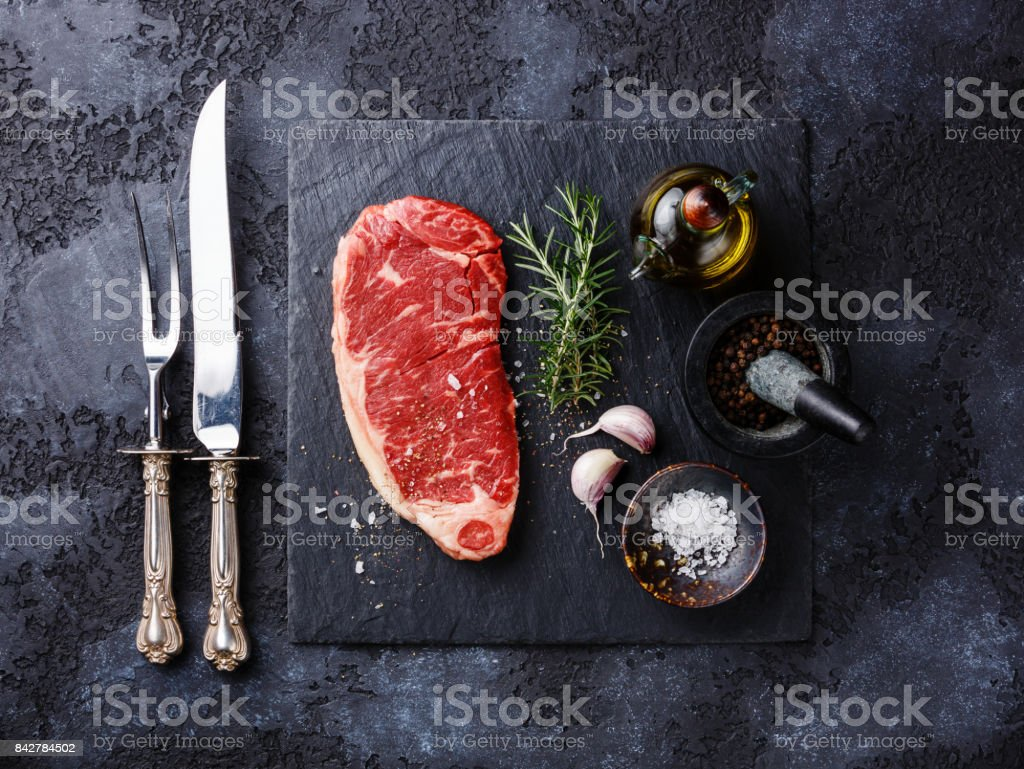 Raw meat steak Striploin, knife and fork and seasonings stock photo