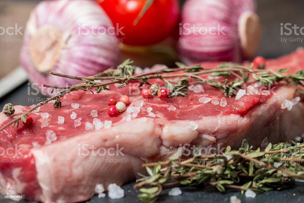 Raw meat steak with fresh herbs and salt stock photo