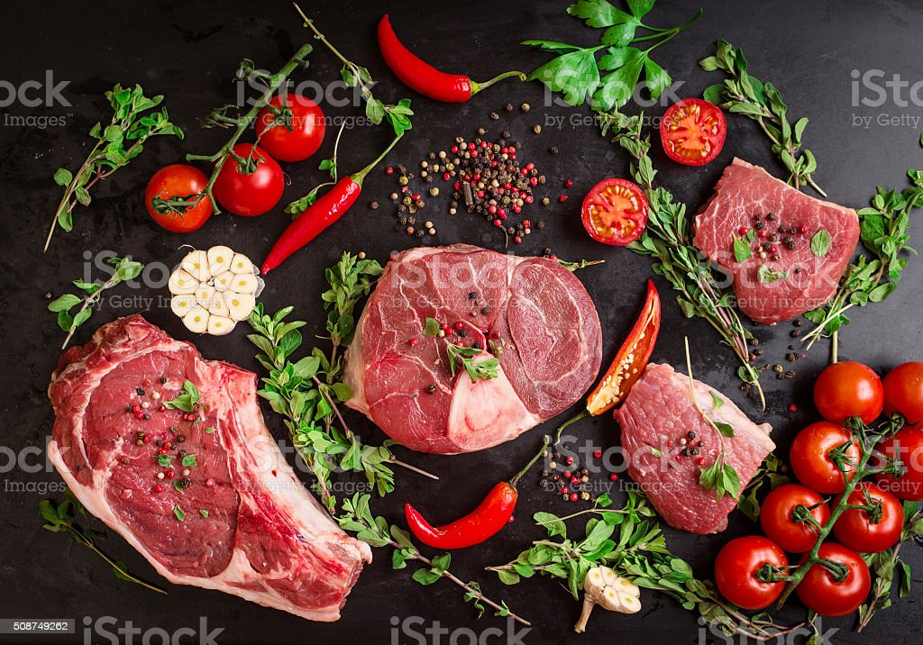 Raw meat steaks on a dark background ready to roasting stock photo