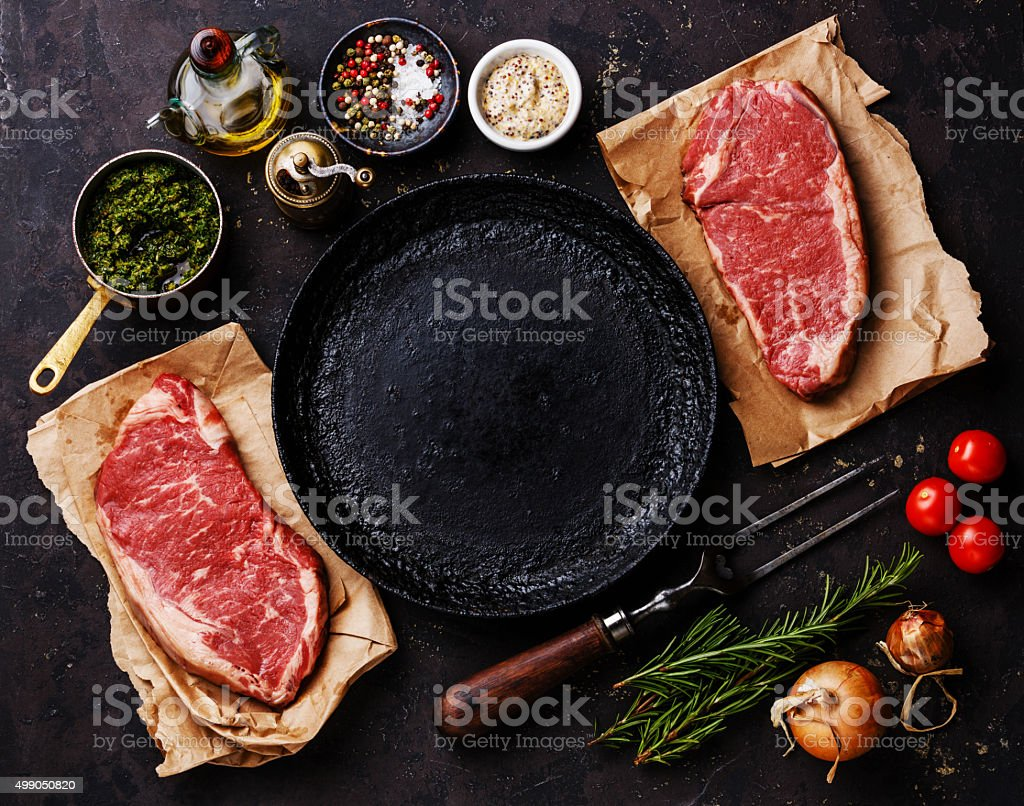 Raw meat steaks with ingredients around pan stock photo