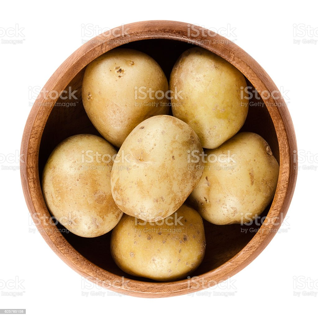 Raw mini potatoes in wooden bowl over white stock photo