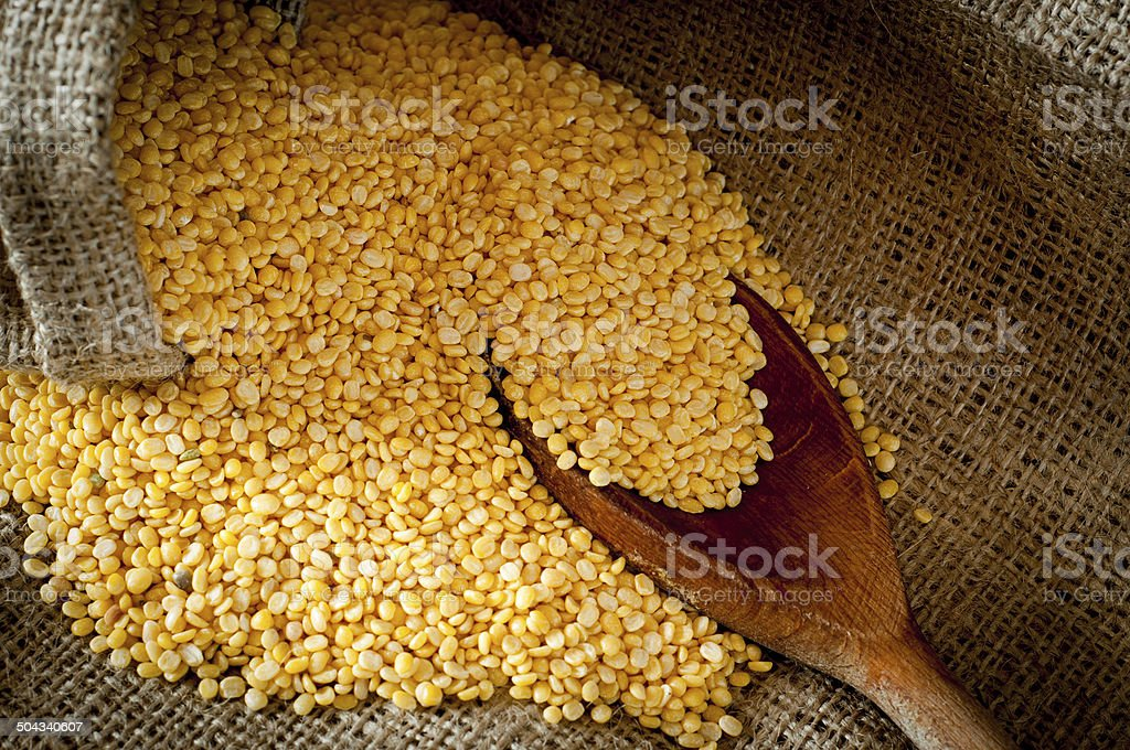 Raw moong dhal in jute bag and wooden scoup stock photo