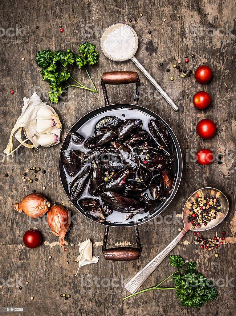 Raw mussels in pan with water on dark wooden background stock photo
