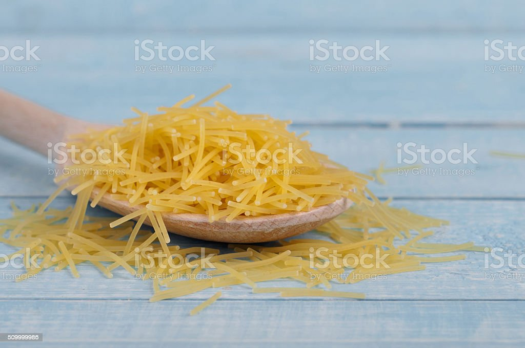 Raw noodles in spoon on a wooden table stock photo